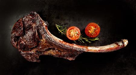 carne de res: Suculenta carne asada tomahawk carne en el hueso con romero fresco y un tomate cereza sobre un fondo negro se ve desde arriba Foto de archivo