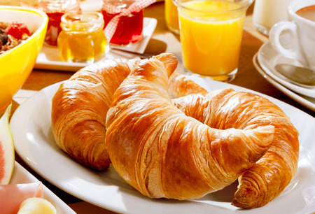 orange juice: Delicious continental breakfast with fresh flaky croissants, assorted preserves, orange juice , cereal and coffee, close up on the croissants