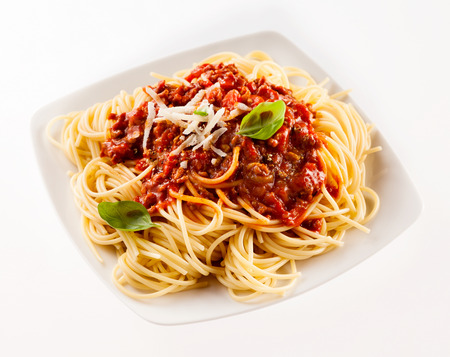 Delicious traditional Italian spaghetti Bolognese with a beef and tomato sauce garnished with fresh basil and grated cheese