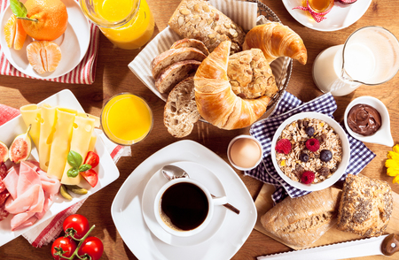 Top view of coffee, juice, fruit, bread and meat on table