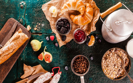preserves: Healthy rustic breakfast with fresh fruit, bread, sausage, milk in a can, coffee, croissants and preserves for a good start to the morning, overhead view