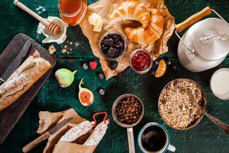 Rustic wholesome healthy breakfast spread out on a green table with coffee, muesli, croissant, baguette, honey, sausage, milk in a can and preserves, overhead view
