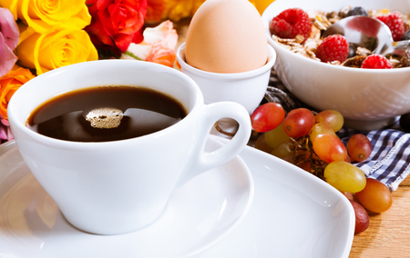breakfast cup: Tasty healthy romantic breakfast with a cup of fresh filter coffee, boiled egg, muesli and bunch of colorful roses