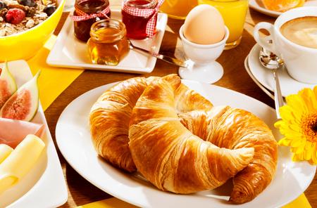 Gezond gezond ontbijt met twee verse croissants op een bord met een gekookt ei, vers fruit en kaas, ontbijtgranen en een kopje koffie, focus naar de croissants