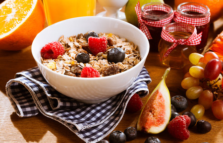 preserves: Healthy muesli with fresh berries and fruit served with freshly squeezed orange juice and assorted preserves for a delicious breakfast Stock Photo