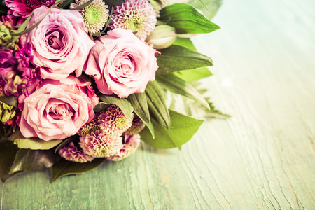 Valentines Day bouquet of beautiful pink and red flowers in top half of frame with copy space over green background