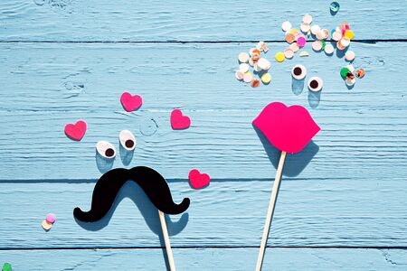 Fun man and woman photo booth accesories with a black mustache making loving eyes at a pair of pink female lips over a rustic blue wooden background