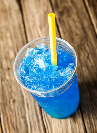 granit: High Angle View of Refreshing and Cool Frozen Blue Fruit Slush Drink in Plastic Cup Served on Rustic Wooden Table with Colorful Yellow Drinking Straw