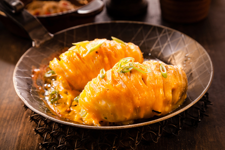 melted cheese: Oven baked sliced potatoes topped with melted cheese and diced spring onion served in a rustic pan for a tasty starter to a meal or lunchtime snack