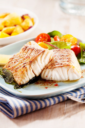 Grilled or oven-baked pollock fillets cooked in a savory marinade and served with a fresh salad and baby boiled potatoes at a seafood restaurant Stock Photo