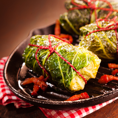 pimientos: Close Up Still Life Detail of Fresh Appetizing Cabbage Rolls Tied with Red String and Served on Sizzling Cast Iron Pan with Red and White Gingham Towel on Rustic Wooden Table