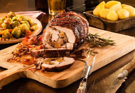 Small pork roast cut and sliced with visible stuffing on cutting board next to dishes of potatoes and brussels sprouts