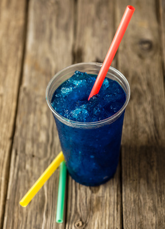 of straw: High Angle View of Refreshing and Cool Frozen Blue Fruit Slush Drink in Plastic Cup Served on Rustic Wooden Table with Collection of Colorful Straws Stock Photo