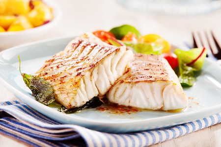 Delicious fillets of pollock or coalfish cooked in a spicy marinade and served with fresh salad and baby potatoes as a seafood appetizer to dinner Imagens