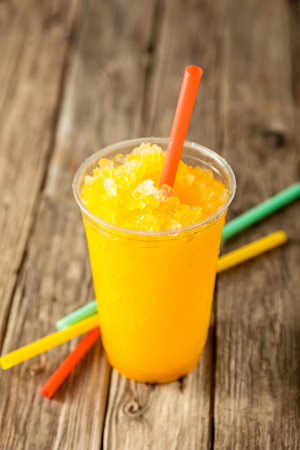slush: Close Up of Refreshing and Cool Bright Orange Slush Drink in Plastic Cup Served on Rustic Wooden Table with Collection of Colorful Drinking Straws Stock Photo