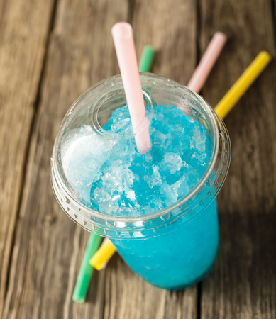 slush: High Angle View of Refreshing and Cool Frozen Turquoise Fruit Slush Drink in Plastic Cup with Lid Served on Rustic Wooden Table with Colorful Drinking Straws