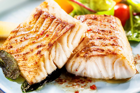 coalfish: Two delicious fillets of marinated grilled or oven baked pollock or coalfish served with a fresh salad, close up view showing the texture