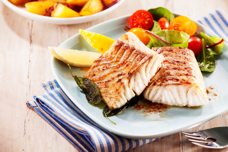 To portions of fresh grilled pollock or coalfish served with colorful salad and slices of lemon, close up high angle view 写真素材