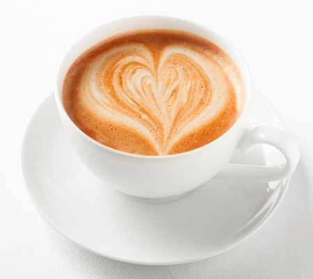 Cup of art cappuccino with a decorative heart pattern in the milky froth served in a generic white cup and saucer viewed high angle