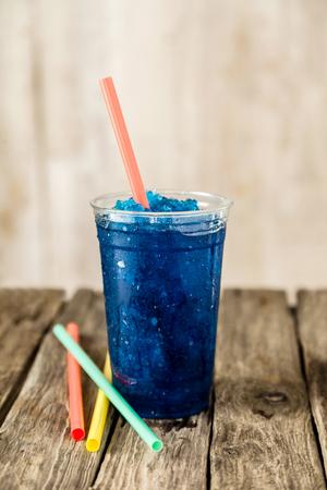 granizados: Aún Perfil Vida de refrescante y fresco congelado Blue Fruit Slush Beber en vaso de plástico que se presentan en la tabla de madera rústica con la Colección de pajitas de colores