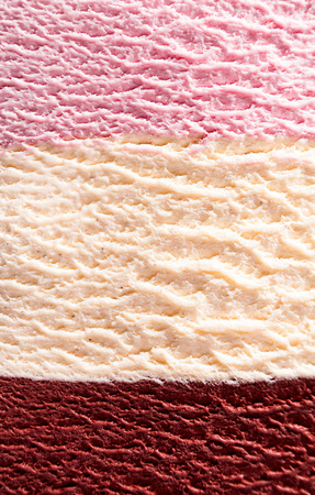 neapolitan: Horizontal close up of stacked strawberry, chocolate fudge and vanilla or Neapolitan flavor ice cream with delicious texture Stock Photo