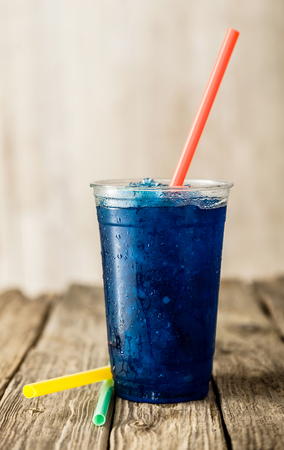 granit: Still Life Profile of Refreshing and Cool Frozen Blue Fruit Slush Drink in Plastic Cup Served on Rustic Wooden Table with Collection of Colorful Straws Stock Photo