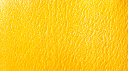Overhead background texture of colorful orange tropical mango sorbet ice cream in a full frame wide angle view