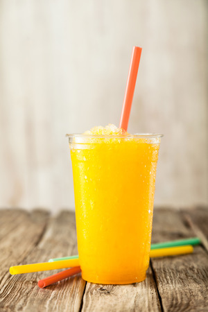 Close Up of Refreshing and Cool Bright Orange Slush Drink in Plastic Cup Served on Rustic Wooden Table with Collection of Colorful Drinking Straws Stock Photo