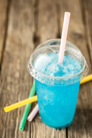 granit: High Angle View of Refreshing and Cool Frozen Turquoise Fruit Slush Drink in Plastic Cup with Lid Served on Rustic Wooden Table with Colorful Drinking Straws