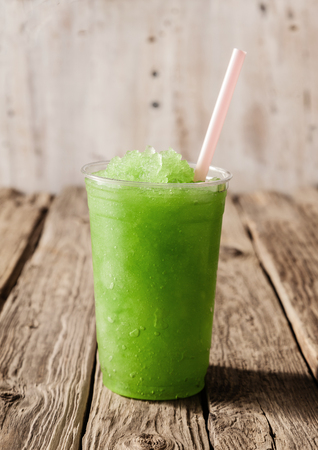 Close Up Still Life of Plastic Cup Filled with Refreshing Frozen Green Slush Drink and Served on Rustic Wooden Table with Drinking Straw Stock fotó
