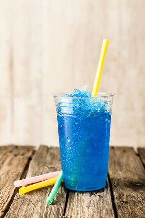 Still Life Profile of Refreshing and Cool Frozen Blue Fruit Slush Drink in Plastic Cup Served on Rustic Wooden Table with Colorful Drinking Straws