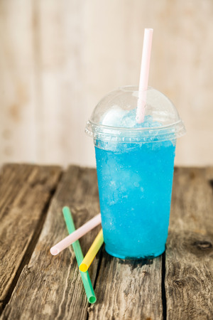 Still Life Profile View of Refreshing and Cool Frozen Turquoise Fruit Slush Drink in Plastic Cup with Lid Served on Rustic Wooden Table with Colorful Drinking Straws