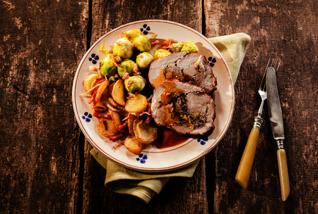 boned: Point of view perspective of single plate filled with sliced stuffed pork roast, potatoes and brussels sprouts over wooden table Stock Photo