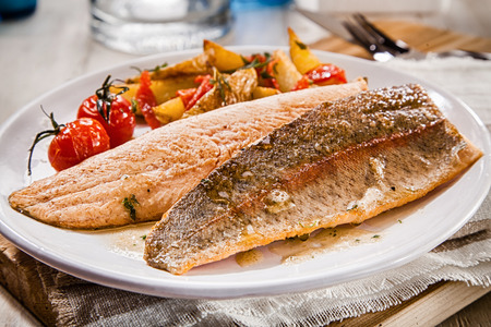 ovenbaked: Healthy grilled or oven-baked fresh salmon fillets rich in omega-3 served with assorted roasted vegetables on a white plate for a tasty seafood dinner