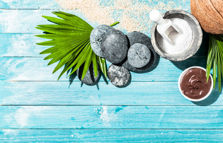 hot rock therapy: Natural spa therapy items as background with various sponges, sea salt, palm leaf and stones over blue wooden panels