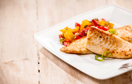 Freshwater fresh grilled and marinated tilapia fillets served with colorful healthy roasted vegetables on a white platter as an appetizer to dinner with copy space on a wooden background