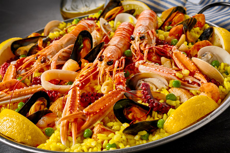 Gourmet seafood Valencia paella with fresh langoustines, clams, mussels and squid on savory saffron rice with peas and lemon slices, close up view