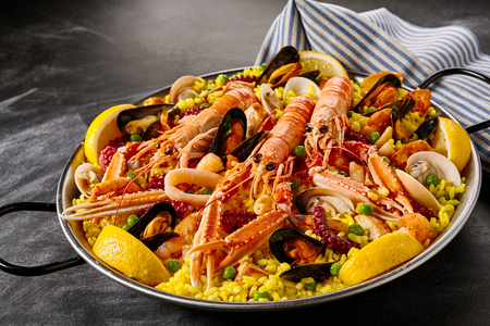 espana: Fresh langoustines in a seafood Valencia paella with clams, mussels and octopus on a bed of saffron rice garnished with lemon slices in a gourmet presentation Stock Photo