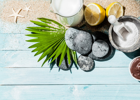 naturopathy: Naturopathy objects as background with coconut milk, lemons, stones, sand, palm leaf and other items over blue wooden panels
