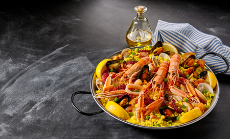 Valencia paella with assorted seafood and shellfish including langoustines, mussels, clams, and squid served with savory seasoned saffron rice and lemon slices, high angle with copy space
