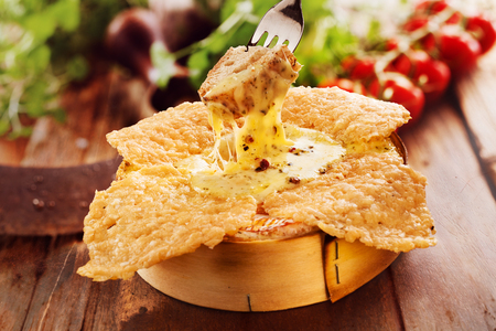 crouton: Person dipping a toasted crouton into a speciality grilled, fried or roast camembert oven cheese dip served in its original wooden box with fresh salad ingredients