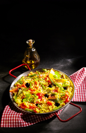 Delicious dish of veggie verduras paella with green asparagus, bell peppers and olives in a bed of yellow saffron rice on a red and white rustic napkin with copy space