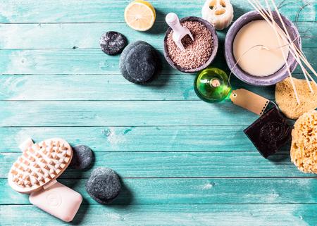 Aromatherapie conceptuele achtergrond met gerangschikte stenen, essentiële oliën, zeezout, sponzen en andere items over blauwe houten panelen