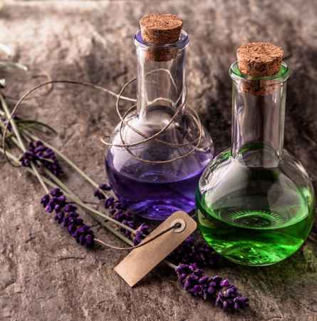 corked: Still Life Close Up of Colorful Purple and Green Essential Aromatherapy Oils in Corked Vials on Textured Stone Surface with Sprigs of Fresh Lavender and Blank Paper Tag