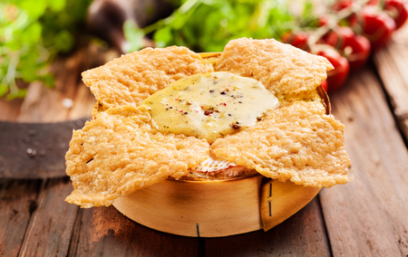 german swiss: Crispy fried or roasted camembert oven cheese dip with a soft succulent center served in its original wooden box with fresh salad ingredients behind on a rustic wooden table