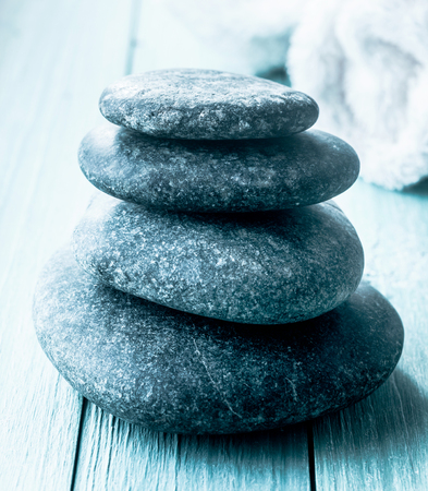 hot rock therapy: Stack of smooth spa stones for a hot rock massage treatment on rustic blue wooden boards with a rolled towel in the background in a conceptual image