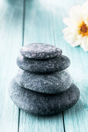hot rock therapy: Stacked smooth round stones for a hot rock spa massage on a blue wooden board background with copy space and a fresh white flower in a wellness concept