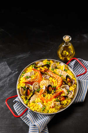 Paella a la margarita in frying pan with red handles on blue and white cloth next to olive oil jar over black