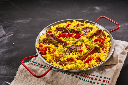 homo: Spanish speciality paella al homo with spare ribs and black pudding on a bed of yellow saffron rice, herbs and red bell pepper served in a metal pan over slate with copy space Stock Photo