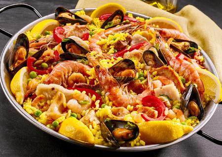 ピンクの海洋エビとムール貝のエンドウ豆とピーマン、黄色いサフラン ライスのグルメ海鮮パエリア クローズ アップ素朴な金属の皿で表示 写真素材 - 51958151